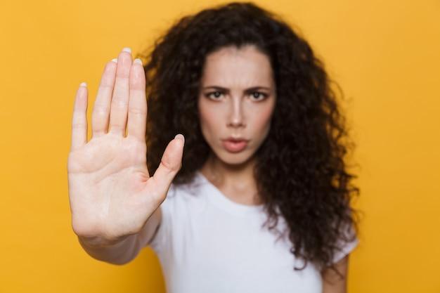 Oburzona kobieta w wieku 20 lat z kręconymi włosami robi gest zatrzymania ręką odizolowaną na żółto