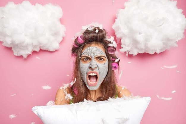 Oburzona młoda europejka krzyczy głośno, jest zirytowana hałaśliwym sąsiadem, który przerywa zasypianie trzyma poduszkę kręcone włosy z wałkami nosi maskę kosmetyczną na twarzy dla odświeżenia skóry