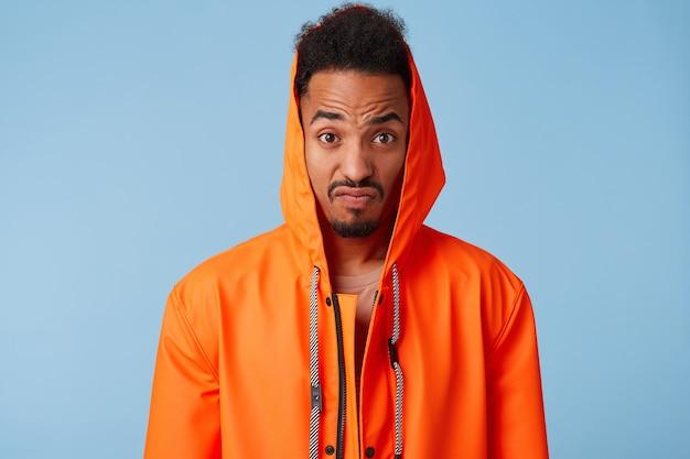 Oburzony afroamerykanin w pomarańczowym płaszczu przeciwdeszczowym zwęża brwi i zaciska usta, wygląda na bardzo niezadowolonego, wstaje.
