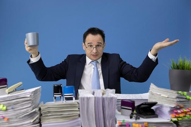 Oburzony biznesmen macha rękami nad biurkiem pełnym dokumentów