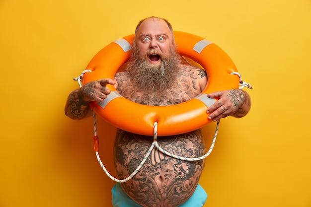 Oburzony, brodaty pulchny mężczyzna krzyczy ze złością, wskazuje wprost, ma wytatuowane ciało, pozuje z nadmuchanym pierścieniem ratunkowym, daje instrukcje pływania,