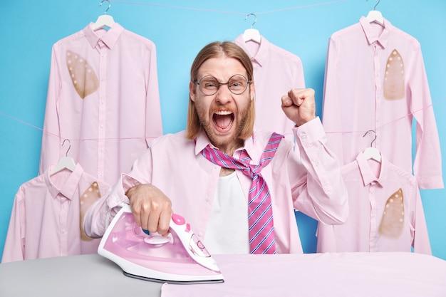 Oburzony mąż domowy zaciska pięści, krzyczy ze złości, bo ma wiele obowiązków zajęty prasowaniem ubrań nosi koszulę i krawat na szyi wyraża negatywne emocje pozuje na wyprasowanych ubraniach