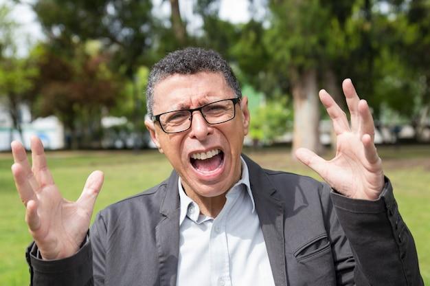 Oburzony mężczyzna w średnim wieku krzyczy i podnosi ręce w parku