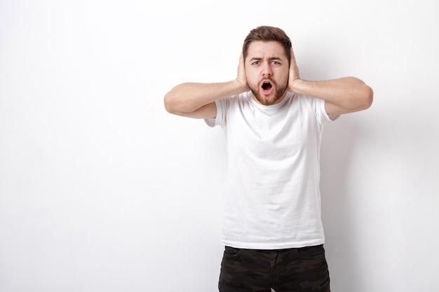 Oburzony młody mężczyzna o ciemnych włosach i brodzie w białej koszulce krzyczy przed białą ścianą