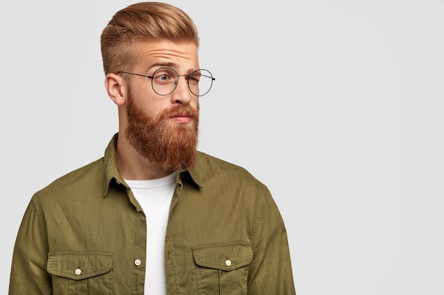 Oburzony rudy mężczyzna patrzy na bok ze zdziwionym, zamyślonym wyrazem twarzy, unosi brwi, nosi okulary, nosi modne ubrania