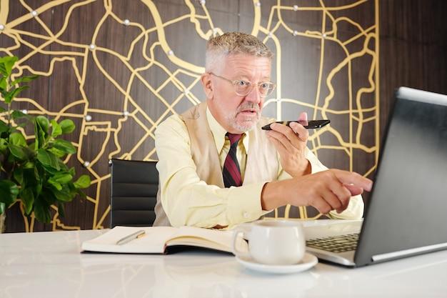 Oburzony starszy przedsiębiorca czytający raport na ekranie laptopa i nagrywający wiadomość głosową dla swojego kolegi lub asystenta