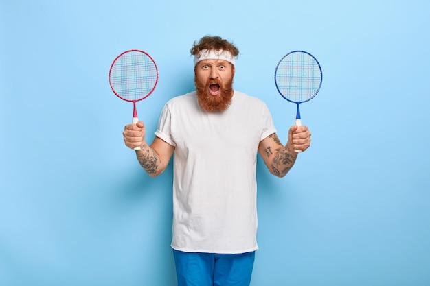 Oburzony wysportowany mężczyzna trzyma dwie rakiety do badmintona, zły przyjaciel nie przyszedł na mecz