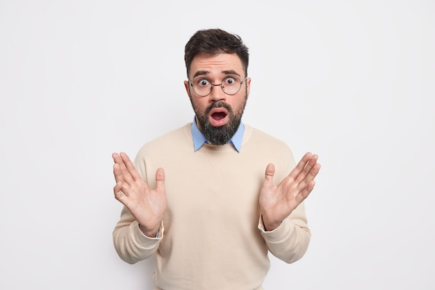 Oburzony, zdziwiony, brodaty dorosły mężczyzna podnosi dłonie, wygląda na zdezorientowanego, ma zdziwiony wyraz twarzy, nie może uwierzyć w coś nieoczekiwanego, nosi swobodny sweter