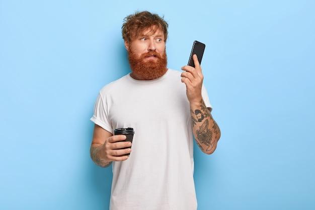 Oburzony, zdziwiony rudowłosy facet pozujący ze swoim telefonem
