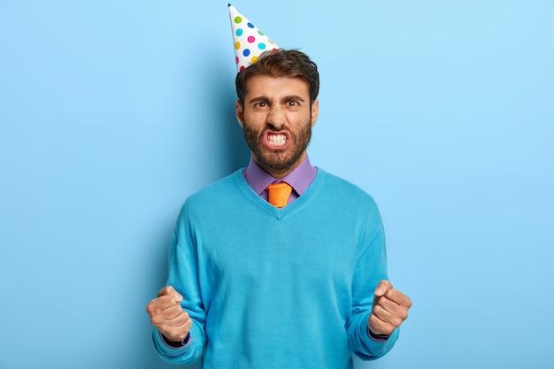 Oburzony zły facet z urodzinowym kapeluszem pozuje w niebieskim swetrze