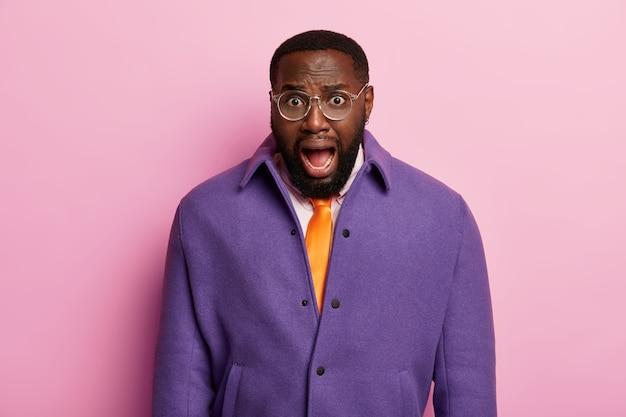 Oburzony zszokowany mężczyzna ma szeroko otwarte usta, ma nieoczekiwaną, zaskoczoną reakcję na coś, niezadowolony z wiadomości, nosi fioletową kurtkę