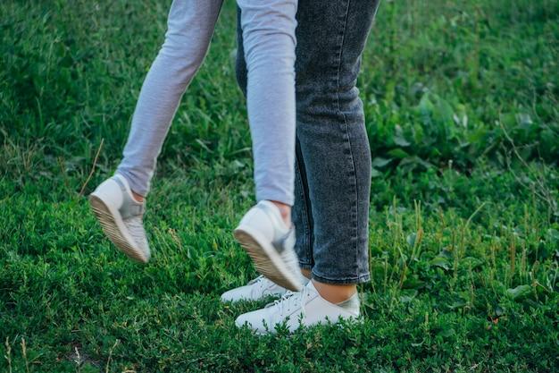 Obuwie damskie i dziecięce na zewnątrz. stylowe zdjęcie damskich butów casualowych na trawie