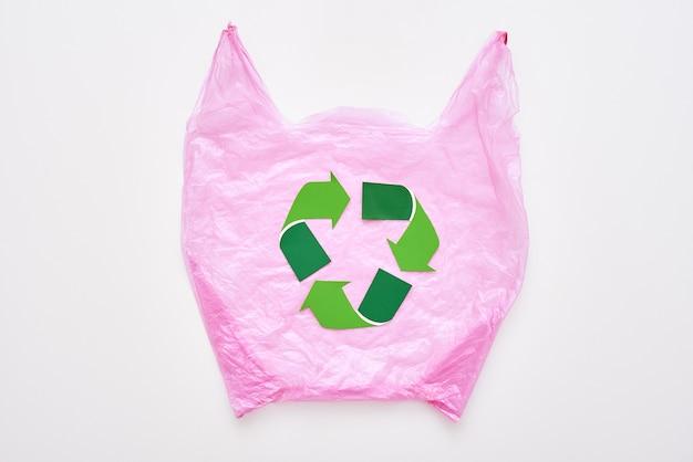 Ocal przyrodę. symbol recyklingu w różowej plastikowej torbie. ponowne użycie znaku redukcji recyklingu. gospodarka odpadami i recykling