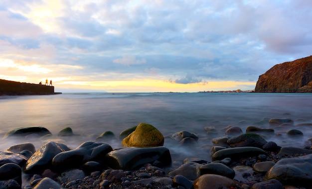 Ocean atlantycki i kamienie na plaży o zachodzie słońca na teneryfie, wyspy kanaryjskie