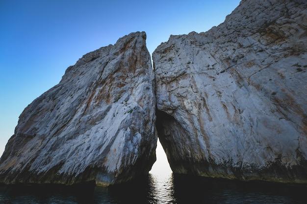 Ocean otoczony skalistymi klifami lśniącymi pod błękitnym niebem - świetny na tapety
