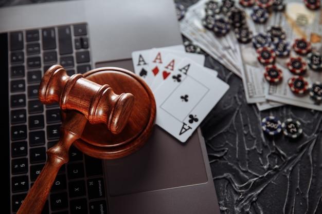 Oceń drewniany młotek i karty do gry na klawiaturze komputera, przepisy prawne dotyczące koncepcji hazardu online.
