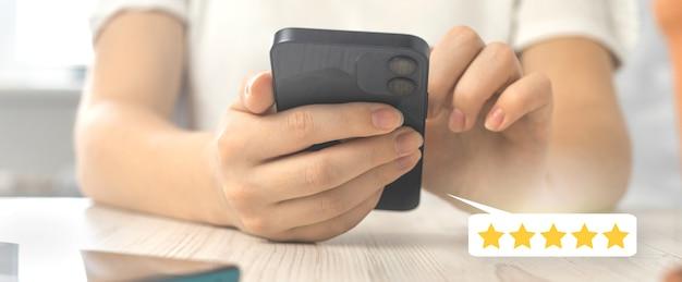 Ocena klienta dobra koncepcja banera oceny, sutomer pięciogwiazdkowa ikona pozytywnej opinii, smartfon w rękach kobiety