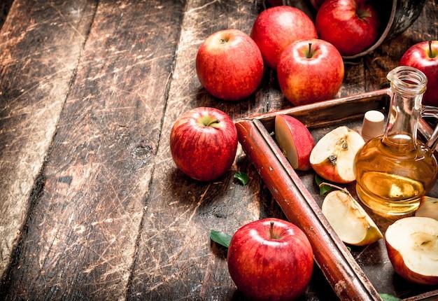 Ocet jabłkowy, czerwone jabłka na starej tacy. na drewnianym stole.