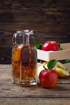 Ocet jabłkowy i świeże czerwone jabłko na drewnianym tle