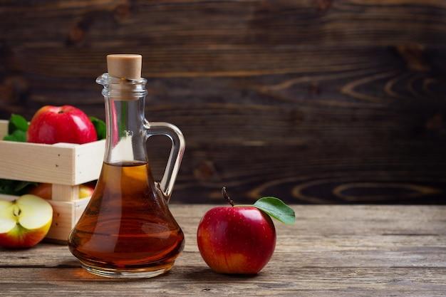 Ocet jabłkowy i świeże czerwone jabłko na tle drewnianych