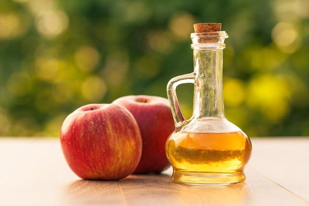 Ocet jabłkowy w szklanej butelce z korkiem i świeże czerwone jabłka na drewnianych deskach z niewyraźne zielone tło naturalne. łuska głębia ostrości. żywność ekologiczna dla zdrowia