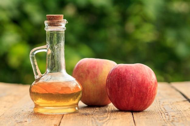 Ocet jabłkowy w szklanej butelce z korkiem i świeże czerwone jabłka na drewnianych deskach z niewyraźnym zielonym naturalnym tłem. żywność ekologiczna dla zdrowia
