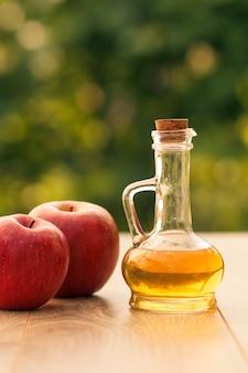 Ocet jabłkowy w szklanej butelce z korkiem i świeże czerwone jabłka na drewnianych deskach z zielonym naturalnym tłem. łuska głębia ostrości. żywność ekologiczna dla zdrowia