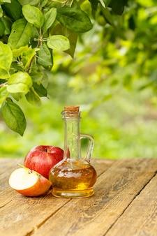 Ocet jabłkowy w szklanej butelce z korkiem i świeże czerwone jabłka na starych drewnianych deskach z niewyraźnym naturalnym tłem. żywność ekologiczna dla zdrowia