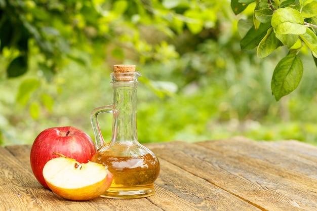 Ocet jabłkowy w szklanej butelce z korkiem i świeże czerwone jabłka na starych drewnianych deskach.