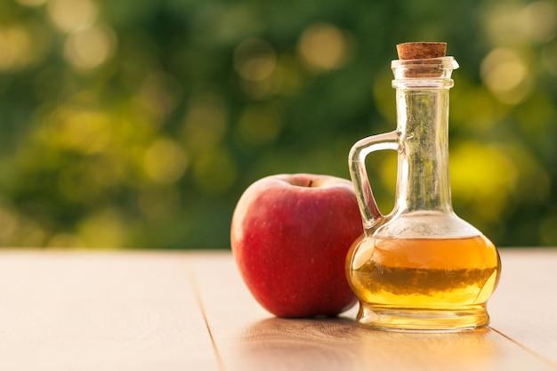 Ocet jabłkowy w szklanej butelce z korkiem i świeże czerwone jabłko na drewnianych deskach z niewyraźne zielone tło naturalne. łuska głębia ostrości. żywność ekologiczna dla zdrowia