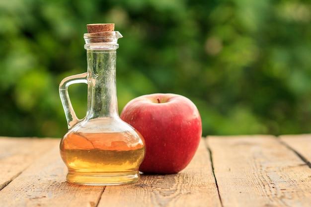 Ocet jabłkowy w szklanej butelce z korkiem i świeże czerwone jabłko na drewnianych deskach z zamazanym zielonym naturalnym tłem. żywność ekologiczna dla zdrowia