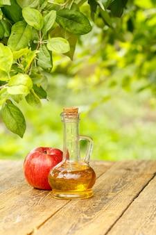 Ocet jabłkowy w szklanej butelce z korkiem i świeże czerwone jabłko na starych drewnianych deskach z niewyraźne zielone tło naturalne. żywność ekologiczna dla zdrowia