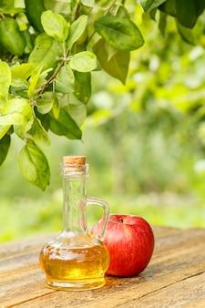 Ocet jabłkowy w szklanej butelce z korkiem i świeże czerwone jabłko na starych drewnianych deskach z zamazanym naturalnym tłem. żywność ekologiczna dla zdrowia