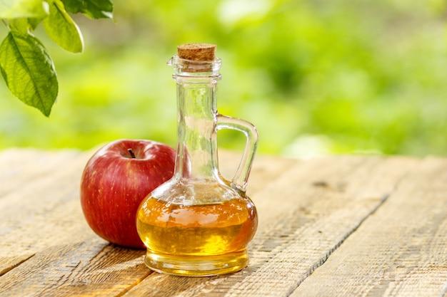 Ocet jabłkowy w szklanej butelce z korkiem i świeże czerwone jabłko na starych drewnianych deskach.