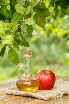 Ocet jabłkowy w szklanej butelce z korkiem i świeże czerwone jabłko na worze i stare drewniane deski z zamazanym naturalnym tłem. żywność ekologiczna dla zdrowia