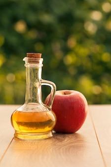 Ocet jabłkowy w szklanej butelce z korkiem i świeżym czerwonym jabłkiem na drewnianych deskach z zielonym naturalnym tłem. żywność ekologiczna dla zdrowia