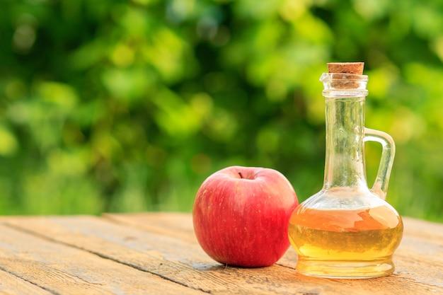 Ocet jabłkowy w szklanej butelce z korkiem i świeżym czerwonym jabłkiem na starych drewnianych deskach z zamazanym zielonym naturalnym tłem