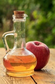 Ocet jabłkowy w szklanej butelce z korkiem i świeżym czerwonym jabłkiem na starych rustykalnych deskach.