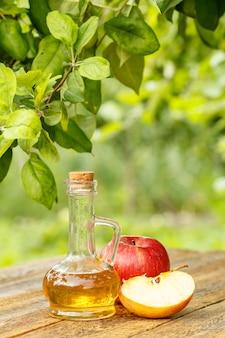 Ocet jabłkowy w szklanej butelce z korkiem i świeżymi czerwonymi jabłkami na starych drewnianych deskach z gałęzią jabłoni i niewyraźnym zielonym naturalnym tłem