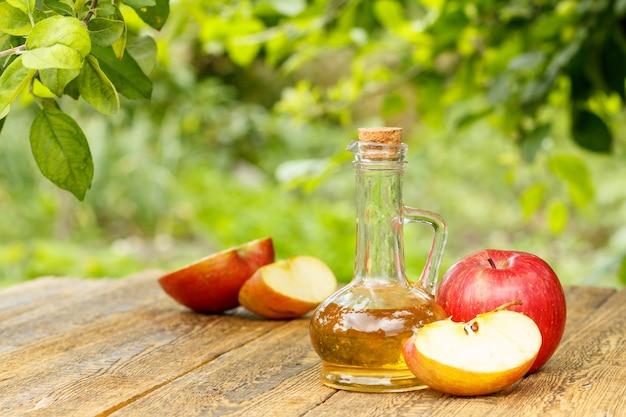 Ocet jabłkowy w szklanej butelce z korkiem i świeżymi czerwonymi jabłkami na starych drewnianych deskach z gałęziami jabłoni i niewyraźnym zielonym naturalnym tłem