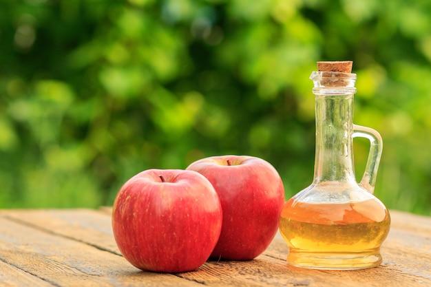 Ocet jabłkowy w szklanej butelce z korkiem i świeżymi czerwonymi jabłkami na starych drewnianych deskach z zamazanym zielonym naturalnym tłem