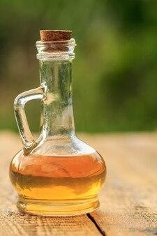 Ocet jabłkowy w szklanej butelce z korkiem na stare rustykalne deski.