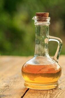 Ocet jabłkowy w szklanej butelce z korkiem na starych drewnianych deskach z niewyraźne zielone tło naturalne. żywność ekologiczna dla zdrowia
