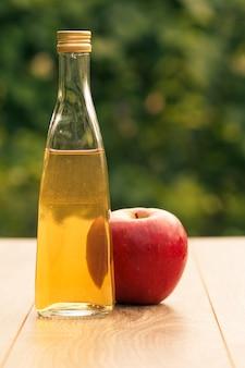 Ocet jabłkowy w szklanej butelce z metalową nakrętką i świeżym czerwonym jabłkiem na drewnianych deskach z zielonym naturalnym tłem. żywność ekologiczna dla zdrowia