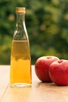 Ocet jabłkowy w szklanej butelce z metalową nakrętką i świeżymi czerwonymi jabłkami na drewnianych deskach z zielonym naturalnym tłem. żywność ekologiczna dla zdrowia
