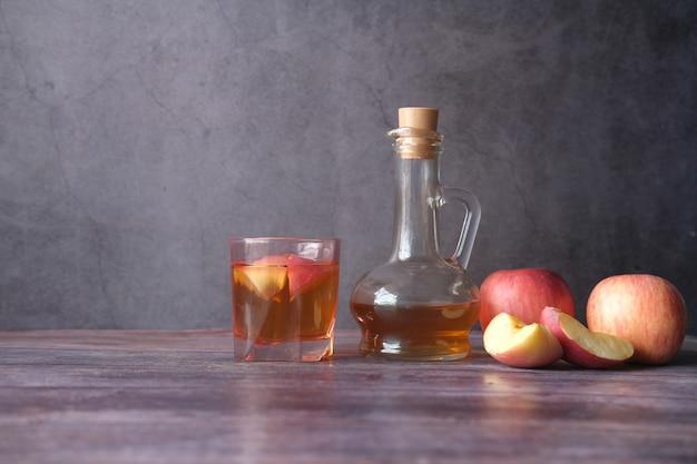 Ocet jabłkowy w szklanej butelce ze świeżym zielonym jabłkiem na stole