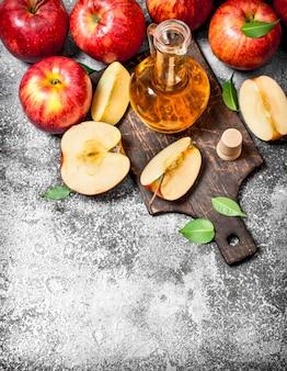 Ocet jabłkowy ze świeżych jabłek na desce do krojenia