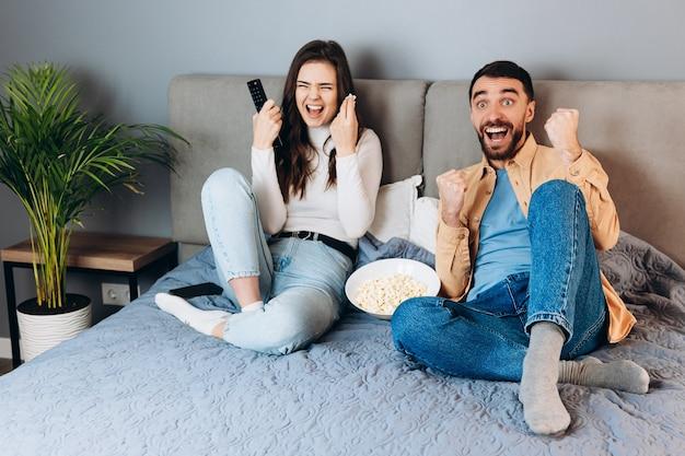 Och, co to jest. słodka młoda para ma czas wolny w kwarantannie oglądać film pod wrażeniem zaskoczenia nieoczekiwanego thrillera kończącego się dużym pudełkiem kukurydzy pop siedzieć na kanapie w domu w pomieszczeniu.