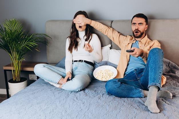 Och, co to jest słodka para ma czas wolny na kwarantannie oglądaj film pod wrażeniem zaskoczona nieoczekiwany thriller kończący się zasłanianiem oczu pudełkiem po kukurydzy siedzieć na kanapie w domu w domu