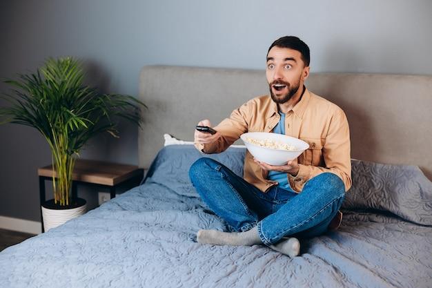 Och, co to jest. zdziwiony człowiek ma czas wolny na kwarantannie oglądaj film pod wrażeniem zdziwiony nieoczekiwany thriller kończący się dużym pudełkiem po kukurydzy siedzieć na kanapie w domu w domu.